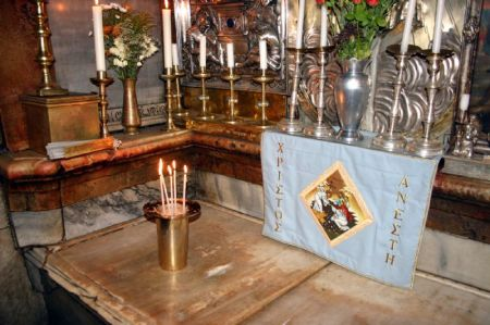 "The holiest site in Christianity: the tomb of Christ inside the edicule of the Church of the Holy Sepulchre. This slab is believed to be where Jesus' body was laid in the tomb. The vase of candles marks the place where his head was. The banner behind it varies with the liturgical seasons: this one is after Easter and says ""Christ is Risen."" Photo © www.HolyLandPhotos.org."