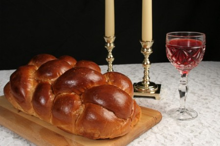 "Shabbat itself is an honored guest, likened to a ""queen,"" in a Jewish household, so the table for the Sabbath meal must be beautiful.  A lovely tablecloth, challah (traditionally braided), wine, and candles all contribute physical graciousness and enhance spiritual enjoyment."